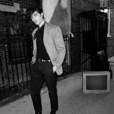 A black and white portrait of Spencer Draeger standing on the street next to an old TV.