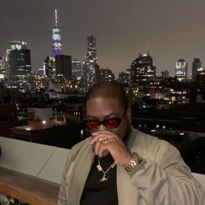 A portrait of Jason Scott Henderson, aka GETOVERHER, on a New York City rooftop at night with the sky in the background