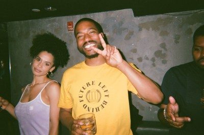 Two party goers looking at the camera, one smiling and making a peace sign