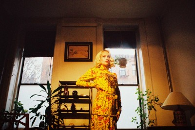 A portrait of Jemima Kirke in a floral print dress standing in a living room