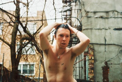 A picture of Alex Cameron dancing shirtless in a Brooklyn backyard