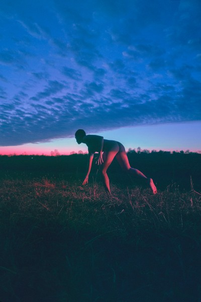 A photograph by Jennifer Medina of a naked person running in a field at sunset