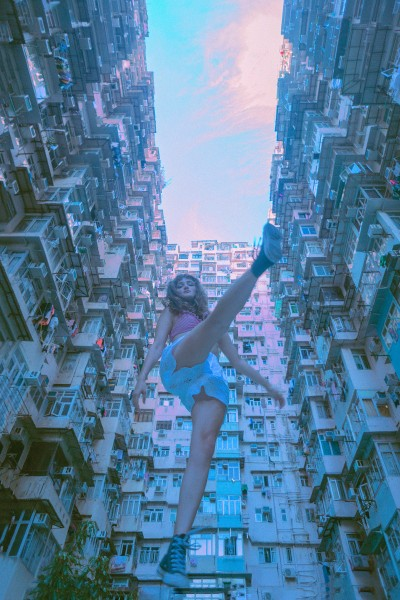 A girl floating in the air surrounded by buildings
