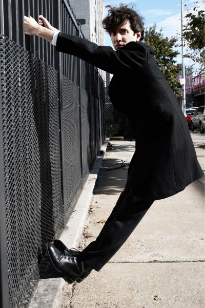 The artist Safer wearing a black overcoat and hanging from a grated fence