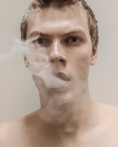 A closeup portrait of a shirtless male model blowing smoke out of his mouth